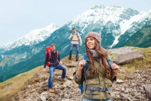 adventure, travel, tourism, hike and people concept - group of smiling friends with backpacks walking down downhill over mountains background