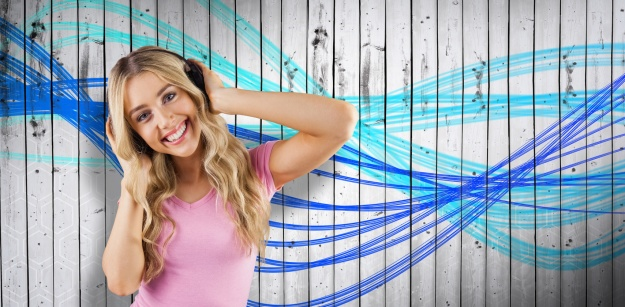 Composite image of portrait of a beautiful woman dancing with headphones